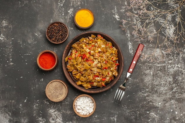 Widok z góry z bliska talerz zielonej fasoli talerz zielonej fasoli i pomidorów obok misek kolorowych przypraw i widelca na ciemnym stole