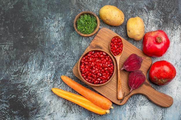 Widok z góry z bliska warzywa deska z nasion granatu marchew buraki ziemniaki zioła