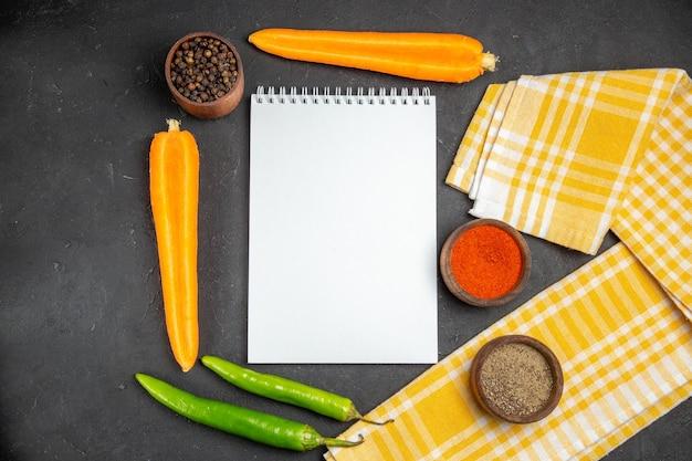 Widok z góry z bliska warzywa notebook obrus w kratkę marchew ostra papryka przyprawy