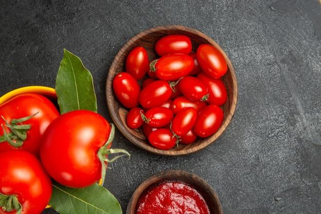 Widok z góry z bliska wiadro z pomidorami miski z pomidorami cherry i keczupem na ciemnym podłożu z wolną przestrzenią