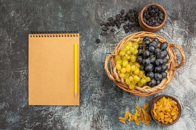 Widok z góry z bliska winogrona kosz winogron między miskami suszonych owoców krem zeszyt ołówek