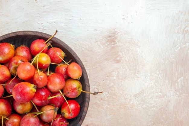 Widok z góry z bliska wiśnie i czereśnie brązowy miska apetycznych wiśni na stole