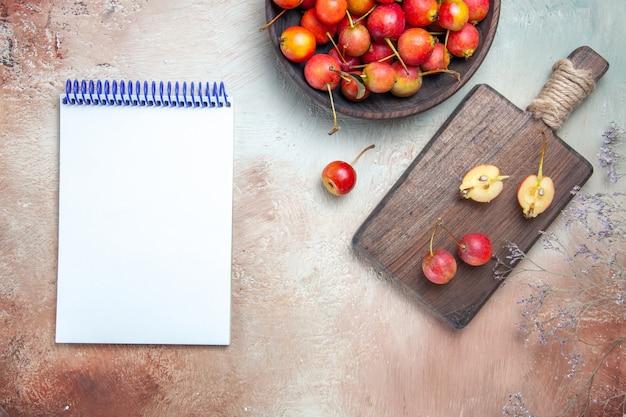 Widok z góry z bliska wiśnie i czereśnie gałęzie drzewa wiśnie w misce i na pokładzie biały notebook