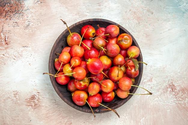 Widok z góry z bliska wiśnie miska czerwono-żółtych wiśni na różowo-biało-szarym stole