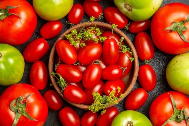 Widok z góry z bliska, wiśniowe, czerwone i zielone pomidory wokół miski z pomidorami cherry i kwiatami kopru na ciemnym podłożu