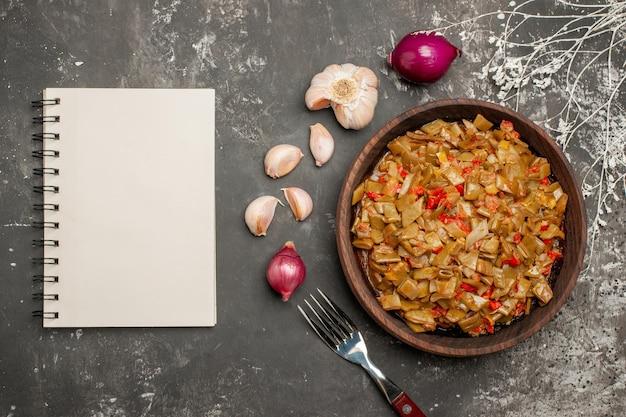 Widok z góry z bliska zielona fasolka z pomidorami drewniany talerz z fasolką szparagową i pomidorami obok białego notatnika z cebulą i czosnkiem i widelcem na stole