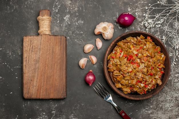 Widok z góry z bliska zielona fasolka z pomidorami drewniany talerz z fasolką szparagową i pomidorami obok deski kuchennej z cebulą i czosnkiem i widelcem na stole