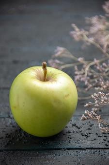 Widok z góry z bliska zielone jabłko apetyczne jabłko obok gałęzi drzew na szarym stole
