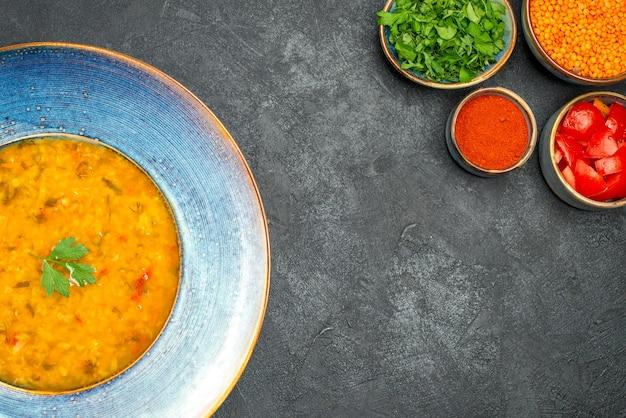 Widok z góry z bliska zupa z soczewicy z ziołami, ziołami, pomidorami, przyprawami