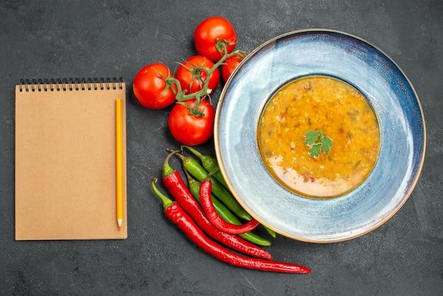 Widok z góry z bliska zupa z soczewicy zupa z soczewicy ostra papryka pomidory z szypułkami ołówek notatnik