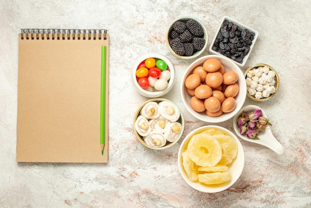 Widok z góry z daleka cukierki w miseczkach apetyczne cukierki i suszone ananasy w miseczkach obok kremowego notatnika i zielonego ołówka