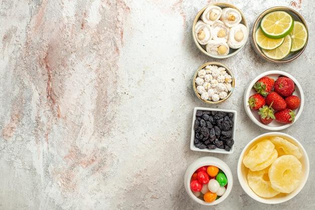 Widok z góry z daleka cukierki w miskach miski różnych słodyczy i suszonych ananasów po prawej stronie białego stołu