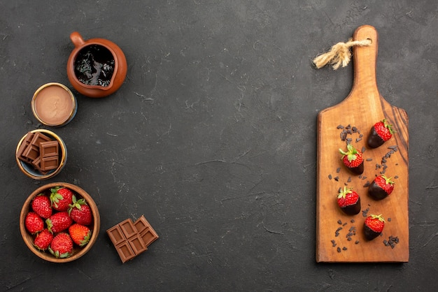 Widok z góry z daleka czekolada i truskawki truskawki i krem czekoladowy po lewej i apetyczne truskawki w czekoladzie na drewnianej desce do krojenia po prawej