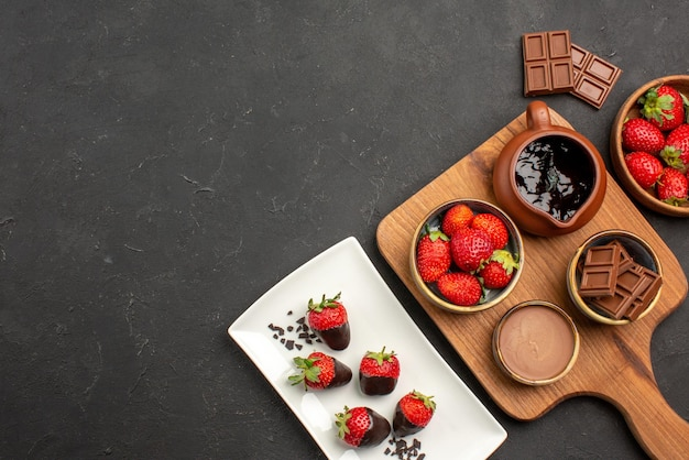 Widok z góry z daleka czekolada na desce truskawki w czekoladzie na talerzu obok deski do krojenia z kremem czekoladowym i truskawkami oraz tabliczkami czekolady
