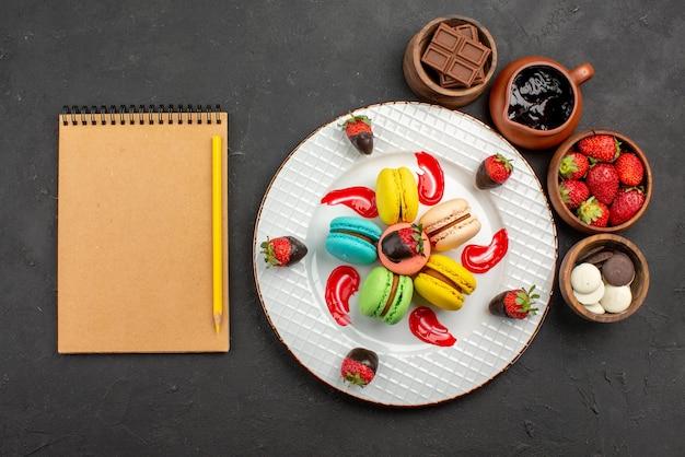 Widok z góry z daleka deser smaczne makaroniki i truskawki obok kremowego notatnika z ołówkiem i miskami z czekoladowymi truskawkami i kremem czekoladowym na stole