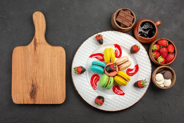 Widok z góry z daleka deserowe makaroniki i truskawki na talerzu obok deski do krojenia i misek z czekoladowymi truskawkami i kremem czekoladowym na stole