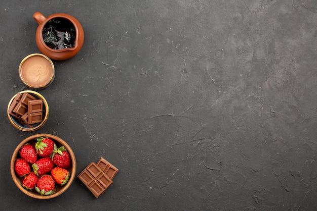 Widok z góry z daleka deserowy krem czekoladowy w misce truskawki i tabliczki czekolady po lewej stronie ciemnego stołu