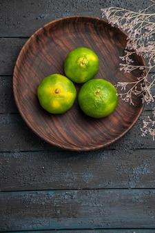 Widok z góry z daleka gałęzie i trzy limonki trzy limonki w brązowej płycie obok gałęzi na szarej powierzchni