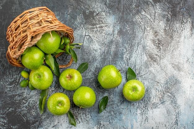 Widok z góry z daleka jabłka zielone jabłka z liśćmi w drewnianym koszu
