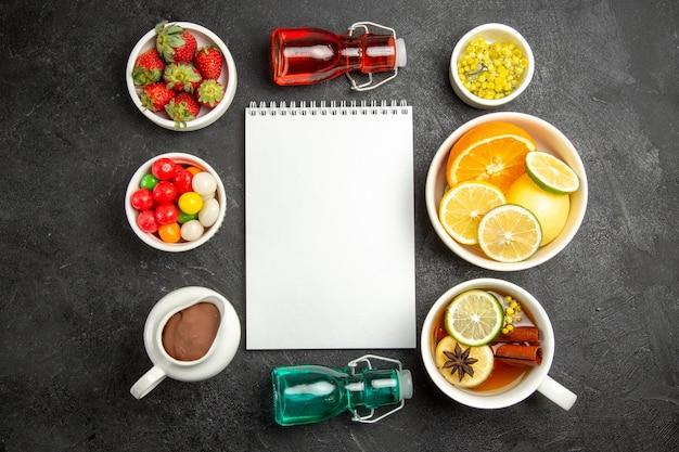 Widok z góry z daleka jagody i miseczki czekoladowe cukierków czekoladowych ziół truskawki i pokrojone cytryny obok białego zeszytu filiżanka herbaty i kolorowe butelki