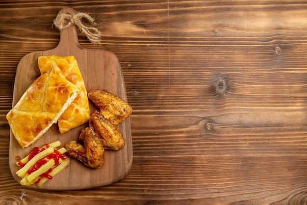 Widok z góry z daleka kurczak i ciasto dwa kawałki placka skrzydełka z kurczaka i frytki z keczupem na desce do krojenia po lewej stronie ciemnego stołu