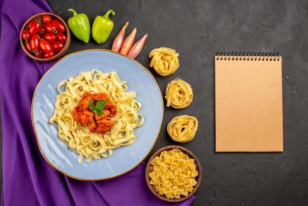Widok z góry z daleka makaron i miska z pomidorami w kulce papryka cebula obok kremowego makaronu zeszyt i talerz makaronu na fioletowym obrusie