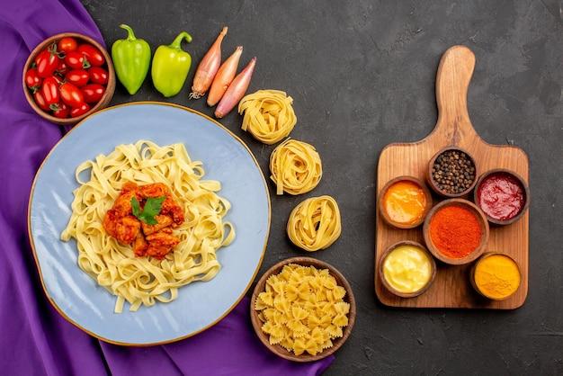Widok z góry z daleka makaron i pomidory talerz makaronu z mięsem i sosem obok pomidorów papryka cebula i makarony obok przypraw i sosów na desce do krojenia na stole