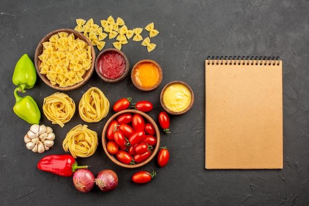 Widok z góry z daleka makarony i sosy pomidory i makarony w miseczkach papryka czosnek trzy rodzaje sosów cebula obok kremu notatnik na stole