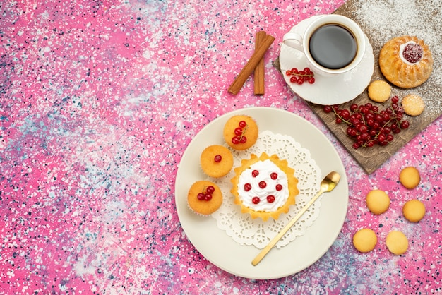 Widok z góry z daleka małe ciasto z kremowymi ciasteczkami świeże żurawiny wraz z filiżanką kawy i cynamonem na kolorowym ciasteczku powierzchni
