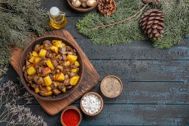 Widok z góry z daleka miska jedzenia miska ziemniaków z grzybami na desce do krojenia obok kolorowych przypraw pod miską oliwy z białymi grzybami i świerkowymi gałązkami
