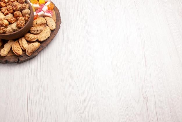 Widok z góry z daleka orzechy na desce różne słodycze i słodkie orzeszki w misce na płycie kuchennej na stole