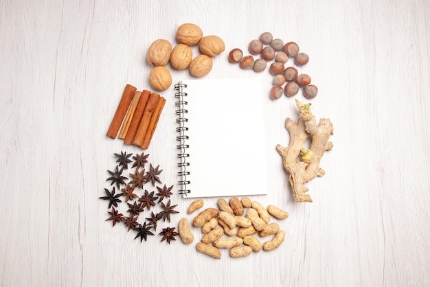 Widok z góry z daleka orzechy różne rodzaje orzechów i laski cynamonu wokół białego notatnika na białym stole