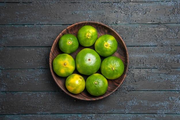 Widok z góry z daleka osiem limonek osiem limonek w drewnianej misce pośrodku szarego stołu