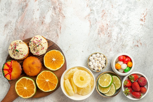 Widok z góry z daleka owoce cytrusowe na desce miski truskawek limonki słodycze i suszone ananasy oraz pokrojona pomarańcza i ciasteczka na drewnianej desce do krojenia