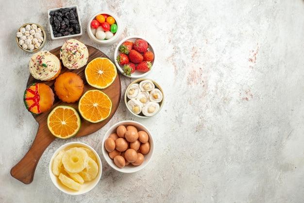 Widok z góry z daleka owoce cytrusowe na desce pokrojone pomarańcze i ciasteczka na drewnianej desce do krojenia obok misek słodyczy i suszonych ananasów