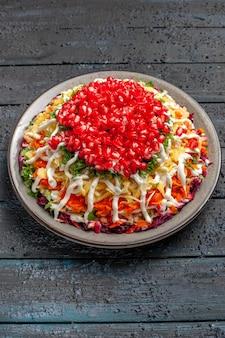 Widok z góry z daleka sałatka z granatem sałatka bożonarodzeniowa z granatem i sosem na talerzu na stole
