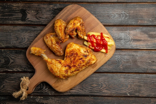 Widok z góry z daleka skrzydełka z kurczaka i udko z kurczaka z frytkami i keczupem na drewnianej desce do krojenia na ciemnym stole