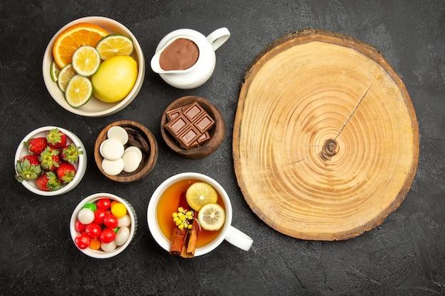 Widok z góry z daleka słodycze na stole filiżanka herbaty z cynamonem i cytryną oraz miski z truskawkami, czekolada i cukierki obok drewnianej deski
