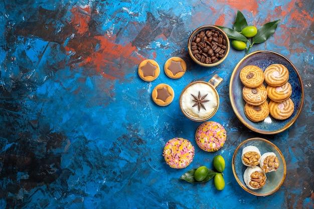 Widok z góry z daleka słodycze różne ciasteczka ziarna kawy owoce cytrusowe filiżanka kawy