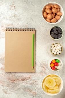 Widok z góry z daleka słodycze w miseczkach apetyczne słodycze w miseczkach obok zielonego ołówka i kremowego notatnika na jasnej powierzchni
