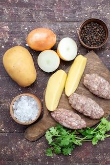 Widok z góry z daleka surowe mięso z surowymi ziemniakami, solą, cebulą, notatnikiem i zieleniną na brązowym biurku, obiad danie z ziemniaków mięsnych