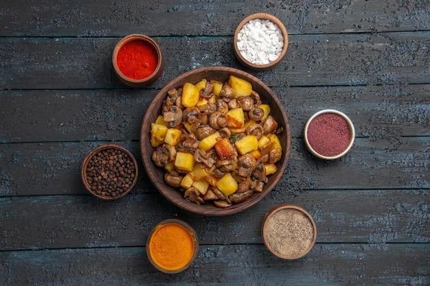 Widok z góry z daleka talerz i miska przypraw z ziemniakami i grzybami oraz kolorowymi przyprawami wokół nich