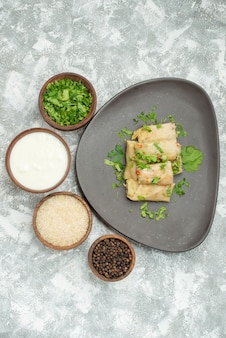 Widok z góry z daleka talerz z miskami z ziół, kwaśną śmietaną, ryżem i czarnym pieprzem, obok szarego talerza gołąbki na stole