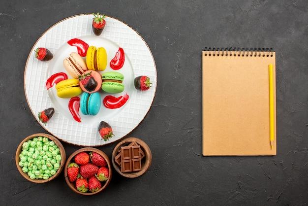 Widok z góry z daleka truskawki i makaroniki talerz apetycznych truskawek sos francuskich makaroników obok zeszytu z ołówkiem i miseczkami słodyczy na ciemnym stole
