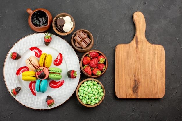 Widok z góry z daleka truskawki i makaroniki talerz truskawek w czekoladzie makaroniki francuskie miski słodyczy wokół niego i deska do krojenia na stole