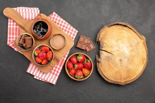 Widok z góry z daleka truskawki i truskawki czekoladowe krem czekoladowy w misce na desce do krojenia na obrusie obok talerza z truskawkami i deski do krojenia