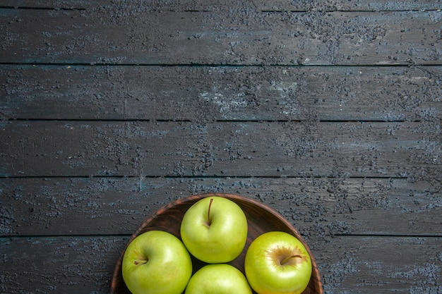 Widok z góry z daleka zielone jabłka siedem zielonych jabłek w misce na ciemnej powierzchni