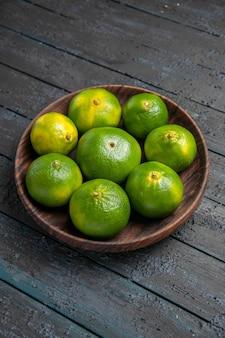 Widok z góry z daleka zielono-żółte limonki na stole zielono-żółte limonki w brązowym talerzu
