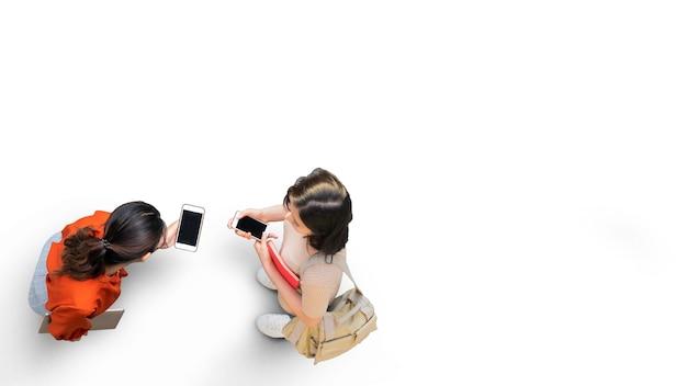 Widok z góry z dwiema studentkami ze stojakiem na smartfona na ulicy z białym chodnikiem z pustą przestrzenią