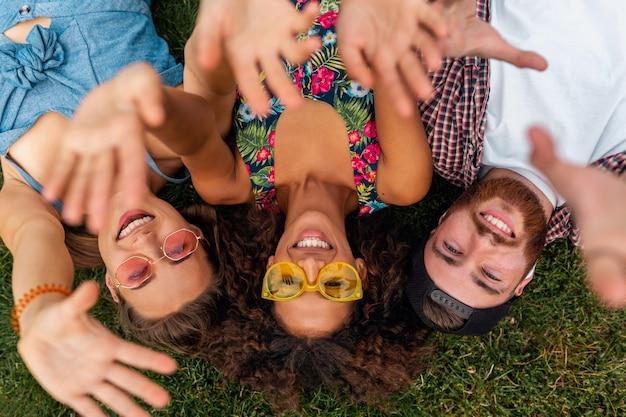Widok z góry z góry na kolorowe stylowe szczęśliwe młode towarzystwo przyjaciół leżących na trawie w parku, mężczyzna i kobiety bawiące się razem